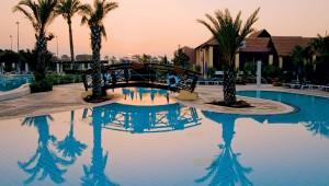 ALDIANA Zypern schöne Poolanlage mit Palmen und Liegen am Abend