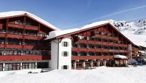 ROBINSON Club Alpenrose Zürs Frontansicht mit Balkon und Eingang im Winter