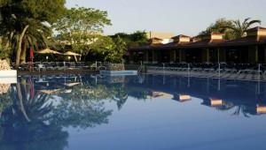 ROBINSON Club Apulia Pool in der Gartenanlage mit Palmen und Liegen