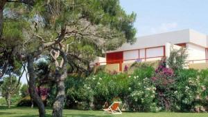 ROBINSON Club Apulia Gartenanlage mit Liegestuhl vor einem Bungalow