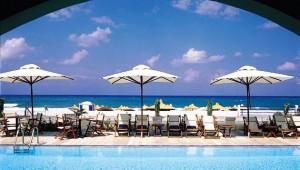 GRECOTEL Plaza Spa Apartments großer Pool mit Liegen und Sonnenschirmen