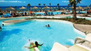 GRECOTEL Olympia Oasis Pool mit Wasserrutschen und Ausblick auf das Meer