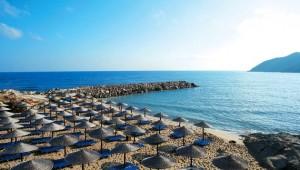 GRECOTEL Marine Palace Suites Strand mit Liegen und Sonnenschirmen