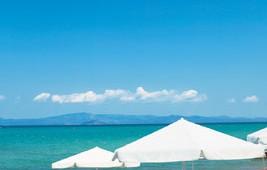 GRECOTEL Pella Beach Ausblick auf den Strand und das Meer mit Sonnenschirm