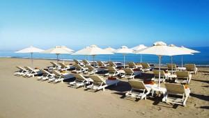 GRECOTEL Plaza Spa Apartments Sandstrand mit Liegen und Sonnenschirmen