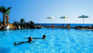 GRECOTEL Marine Palace Pool mit Felsen und Palmen sowie direktem Meerblick