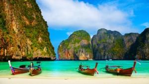 Thailand Rundreise Tropischer Strand und die traditionellen Boote in der Bucht